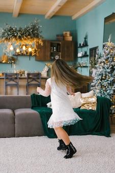 Девушка с длинными волосами в белом платье крутится в гостиной с елкой