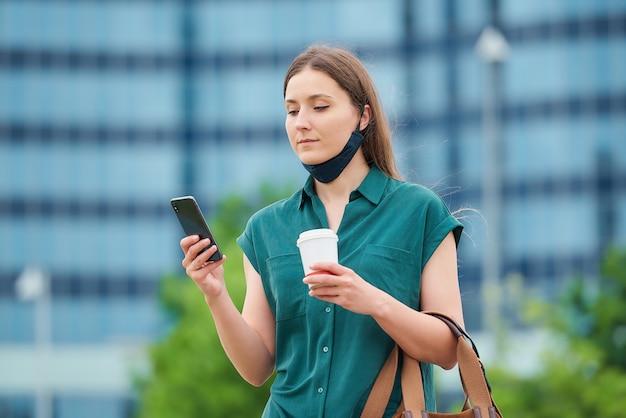 긴 머리를 가진 소녀는 스마트 폰에서 뉴스를 읽고 시내에서 커피를 마시고 있습니다.