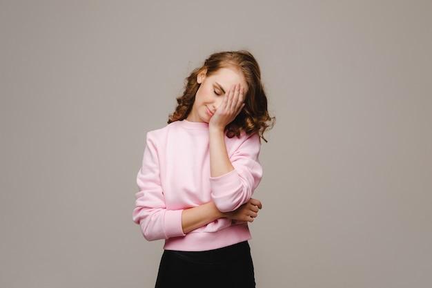 두통으로 고통받는 회색 배경에 긴 머리를 가진 소녀는 그녀의 손으로 그녀의 머리를 잡고