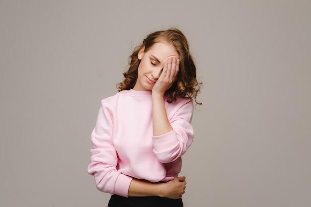 두통으로 고통받는 회색 벽에 긴 머리를 가진 소녀는 그녀의 손으로 그녀의 머리를 잡고