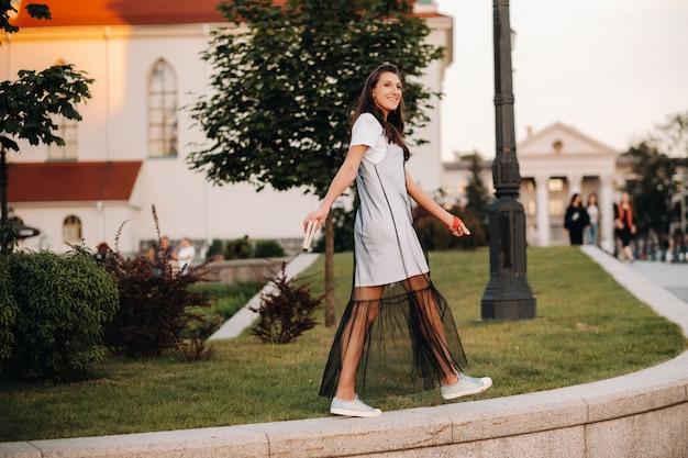 長い髪の赤いイヤリングと白い服を着た女の子が、本を手に街を歩き回っています。