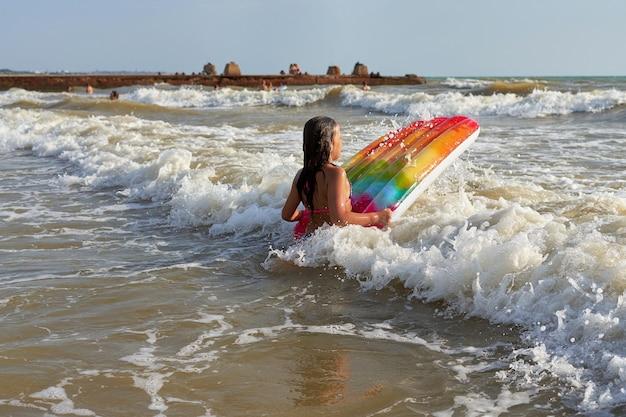 長い髪の少女がマルチカラーのインフレータブルマットレスで海の波に足を踏み入れる