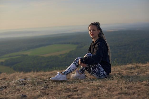 黒のパーカーに長いおさげ髪の女の子が崖の上に座って、まっすぐにキャマーをのぞきます...