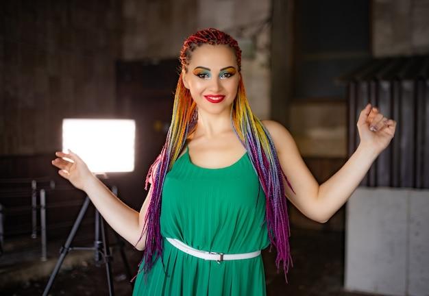 Девушка с макияжем и разноцветными африканскими косичками в зеленом платье мило улыбается гуляя по улицам весеннего города