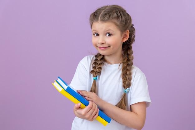 白いtシャツを着たおさげ髪と孤立した壁に彼女の手で本を持っている女の子。