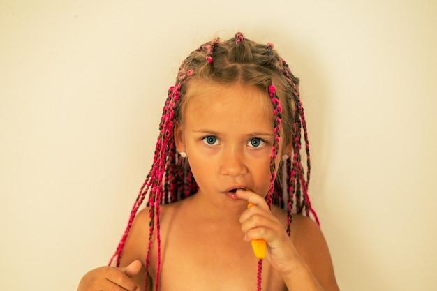 Девушка с розовыми косичками чистит зубы