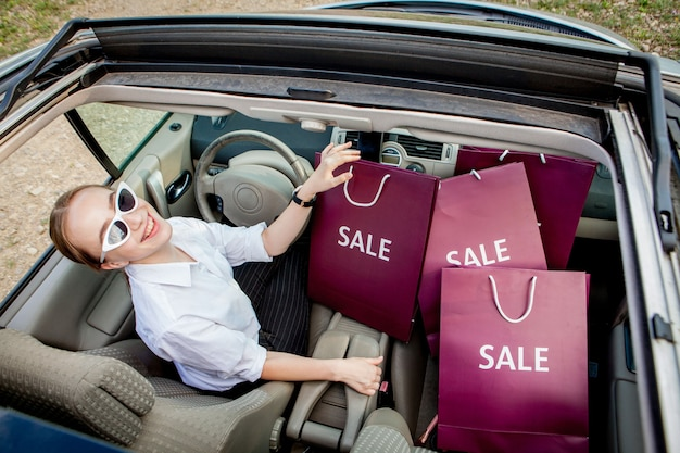ショッピングバッグを持った女の子が車を運転しています