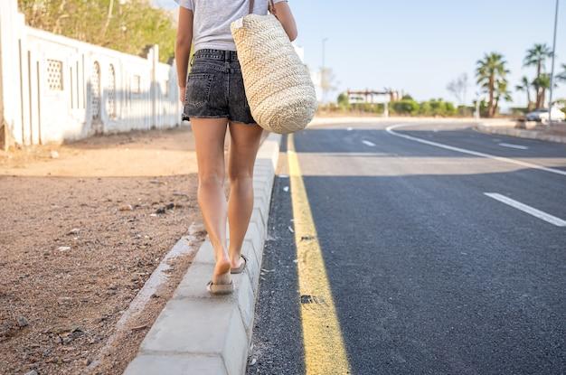 日焼けした足の女の子が、バッグを持って道路沿いの歩道を歩いています。