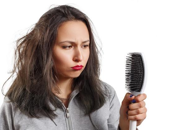 Девушка с растрепанными лохматыми волосами держит в руках расческу. проблемы с волосами, кожей головы и перхотью, изолированные на белом
