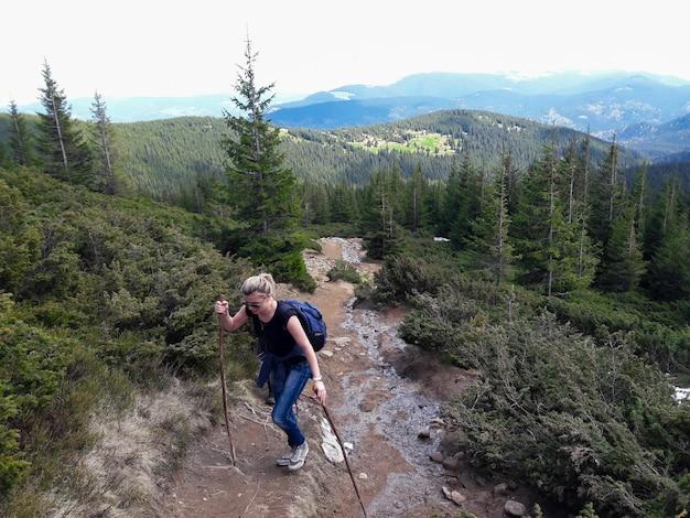 暖かい季節に杖とバックパックを持った少女が山を登る