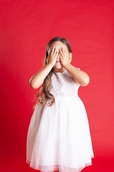 ウェーブのかかった髪と白いドレスの女の子が驚きを待っている彼女の手で目を覆っている