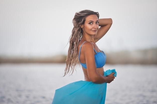 Девушка с мокрыми волосами в синем купальнике и парео греется на солнышке после купания в лимане.