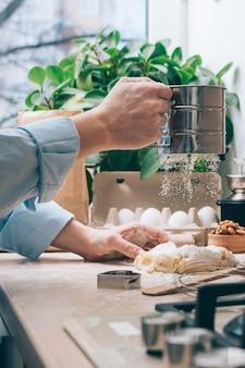 顔のない女の子が生地を用意し、小麦粉をまぶしてクローズアップ。自宅のキッチンで自家製ケーキを作る。料理の背景。