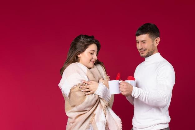 Девушка, завернутая в плед, пьет чай с мужчиной на красном фоне.