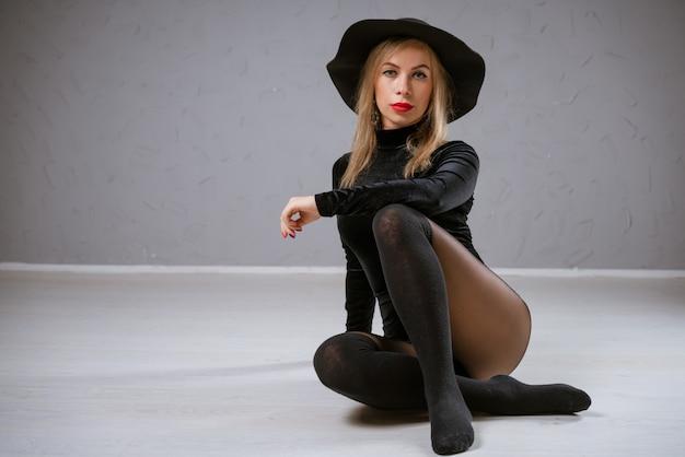 バックグラウンドで黒いボディースーツと黒い帽子の魅力的な女性ポーズ