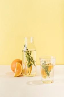 오렌지와 로즈마리가 첨가 된 유리 잔과 깨끗한 물 한 병. 건강한 비타민이 들어간 상쾌한 음료. 텍스트 복사 공간이있는 세로 방향입니다.