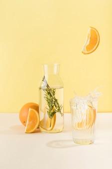 Стакан и бутылка чистой воды с добавлением апельсина и розмарина. апельсин падает в стакан с брызгами воды. вертикальная ориентация с копией пространства для текста.