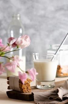 유리와 우유 시리얼 한 병은 분홍색 꽃이 든 항아리에 아몬드를 바릅니다.