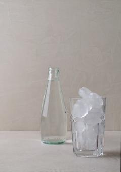 ベージュの背景に水のガラス瓶が立っています。氷のあるぼやけたフォーカスグラスで、スペースをコピー