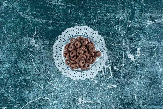 青いテーブルの上のキャスターの上のトウモロコシのリングのガラスのボウル。