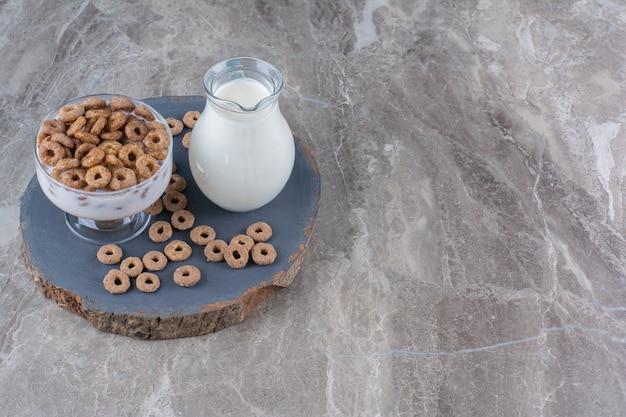 바삭한 시리얼과 우유 한 병이 들어 있는 건강한 요구르트 유리 그릇.