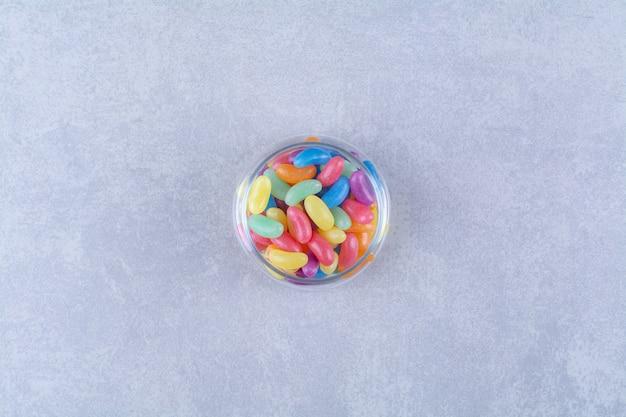 灰色の背景にカラフルな豆菓子でいっぱいのガラスのカップ。高品質の写真
