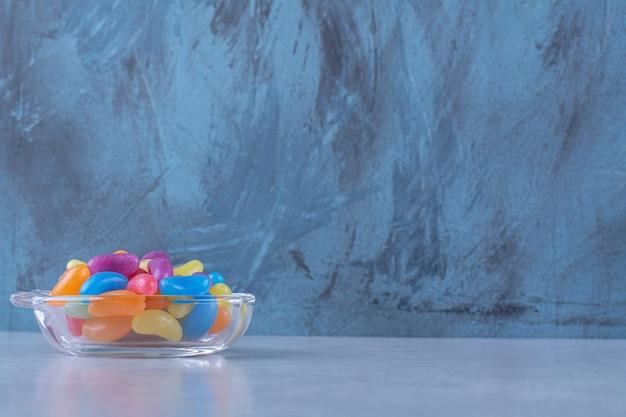 회색 표면에 다채로운 콩 사탕으로 가득 찬 유리 컵. 고품질 사진