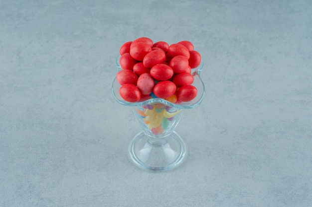 Стеклянная чашка, полная конфет красочные фасоль на белом фоне. фото высокого качества