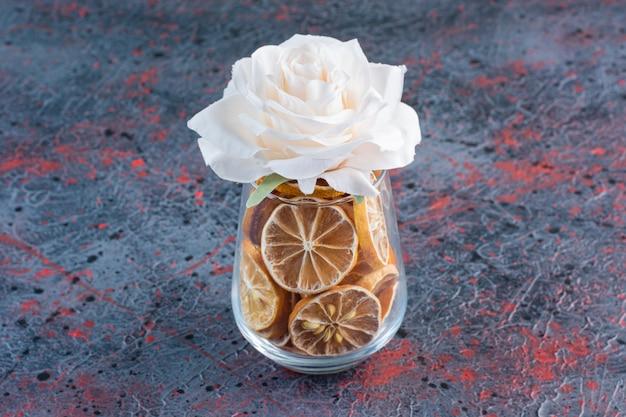 머리 위로 말린 레몬과 분홍 장미가 가득한 유리 컵.