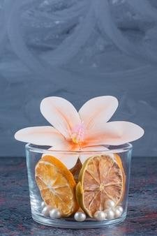 Стеклянная чашка, полная сушеного лимона с цветком и жемчугом на сером фоне.
