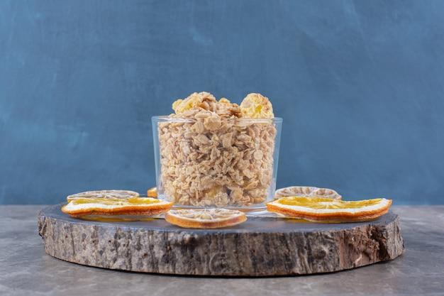 말린 오렌지 과일 조각으로 건강한 콘플레이크 가득한 유리 컵.