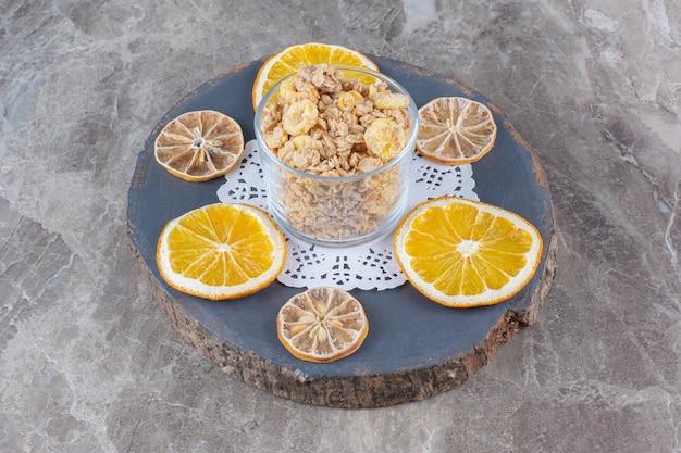 乾燥したオレンジ色の果物のスライスと健康的なコーンフレークでいっぱいのガラスのカップ。