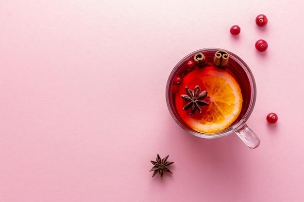 Стеклянная чашка рождественского глинтвейна или глога на розовой поверхности