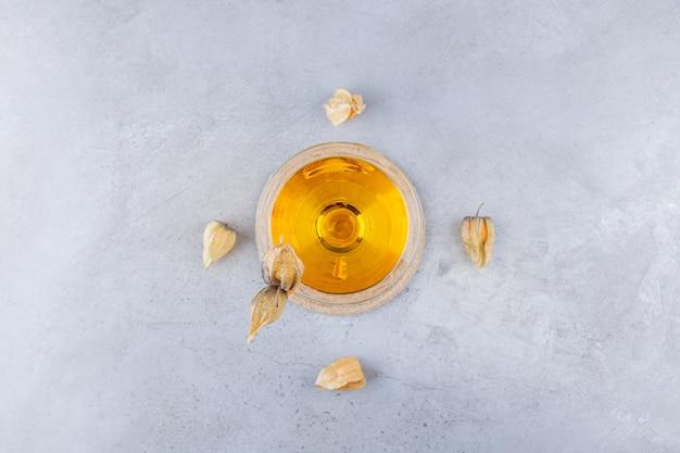 돌 테이블 위에 놓인 말린 커 쿼트 과일과 함께 신선한 주스의 유리 컵.