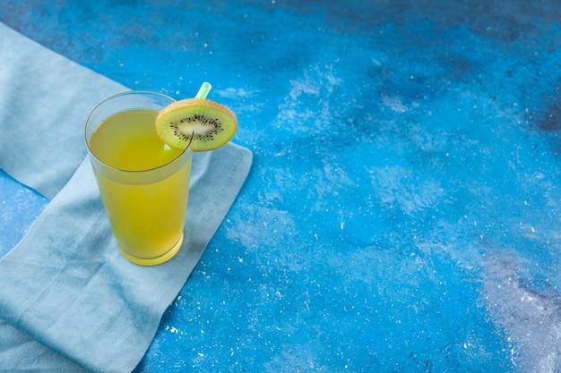 Стеклянный стакан свежего сока с соломинкой на скатерти