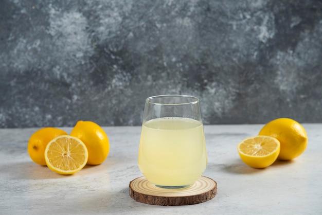 木の板に新鮮なレモンジュースのガラスカップ。