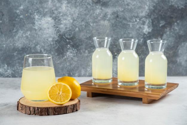 Стеклянный стакан свежего лимонного сока на деревянной доске.
