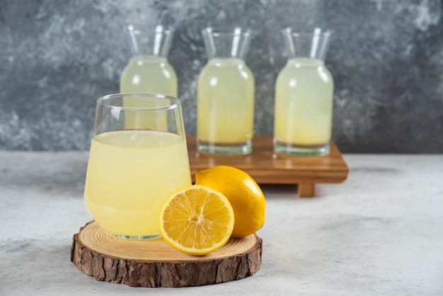 나무 보드에 신선한 레몬 주스의 유리 컵.