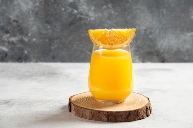 木の板に新鮮なオレンジジュースのガラスカップ。
