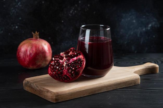 나무 보드에 신선한 석류 주스의 유리 컵.