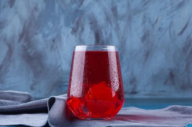 テーブルクロスの上に置かれたフルーツジュースのガラスカップ。