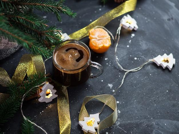 Стеклянная чашка горячего кофе эспрессо на столе, гирлянда в виде елки, ветки. домашняя атмосфера и уют