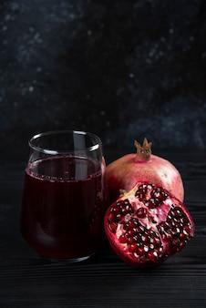 어둠에 석류와 주스의 유리 컵.