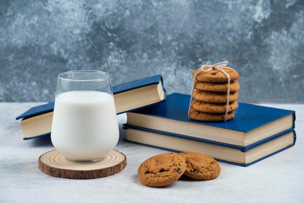 나무 보드에 초콜릿 쿠키와 우유의 유리 컵.