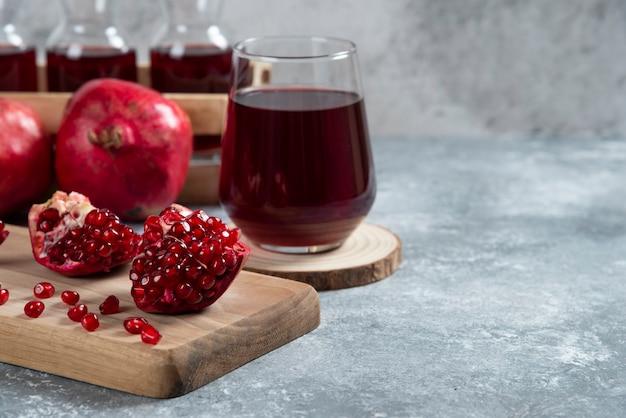나무 보드에 석류 주스의 유리 컵.