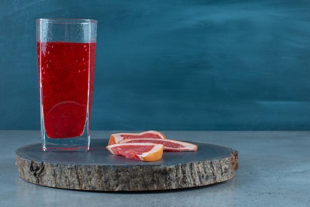 グレープフルーツのスライスと赤いジュースのガラスカップ。