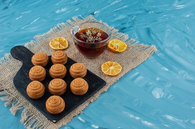 荒布の上にクッキーと乾燥スライスレモンとお茶のガラスカップ。