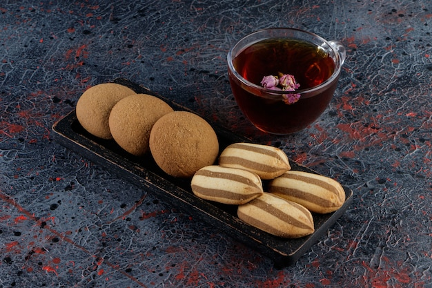 Стеклянная чашка чая со сладким свежим печеньем на доске на темноте