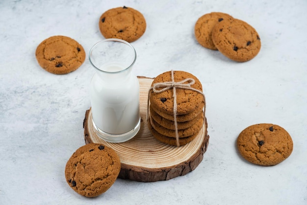 나무 책상에 초콜릿 쿠키와 유리 컵.