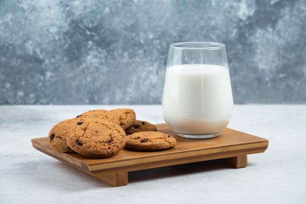 木製の机の上にチョコレート クッキーが入ったガラス カップ。